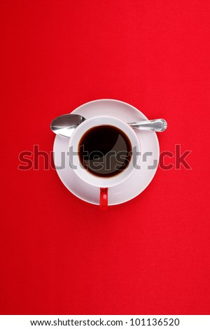Coffee cup, saucer and spoon on a red background