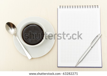 Coffee cup, spiral notebook and pen on the wooden table