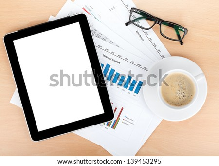 Coffee cup, tablet and glasses over papers with numbers and charts. View from above