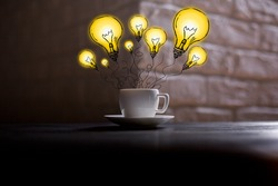 Coffee cup with abstract drawn lamps placed on dark wooden table and blurry brick corner background. Idea concept