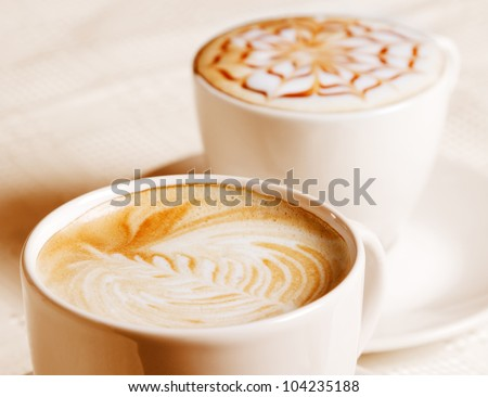 Coffee cup with artistic cream decoration, isolated on white background