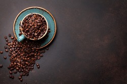 Coffee cup with beans on stone background. Top view with copy space for your text