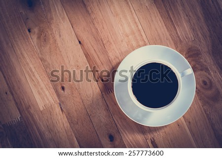 Coffee cup with black coffee on wooden table (top view) - soft focus with vintage color effect
