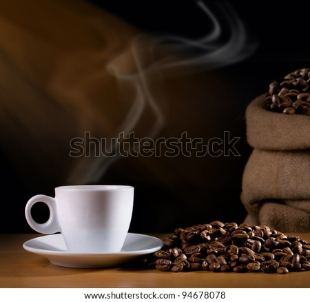 Coffee cup with burlap sack of roasted beans - stock photo
