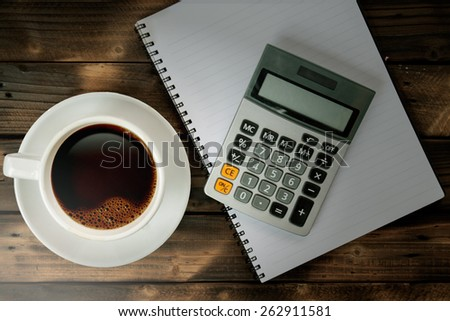 Coffee cup with calculator and notebook on Working desk