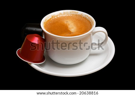 Coffee cup with capsules isolated on black