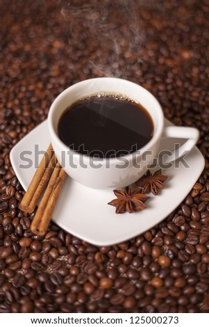 Coffee cup with cinnamon and anise spices with coffee beans background
