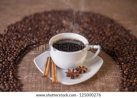 Coffee cup with cinnamon and anise stars over canvas background with coffee beans