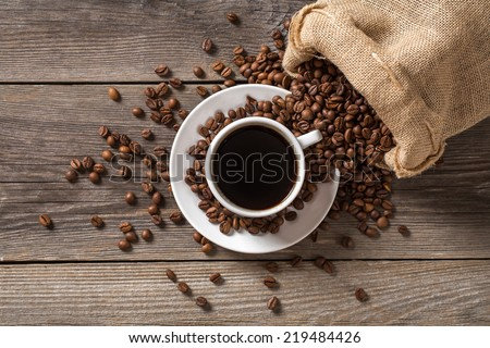 Coffee cup with coffee bag on wooden table. View from top.