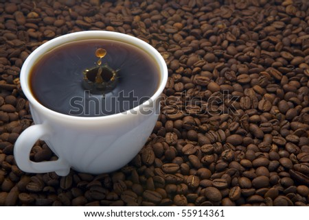 Coffee cup with drop on beans background
