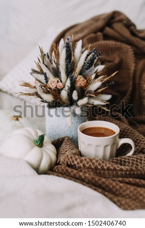 Coffee cup with flowers and pumpkins on a cozy plaid. Autumn still life. Breakfast in bed. Good morning. Stylish autumn flat lay. Hello fall. Cozy warm image