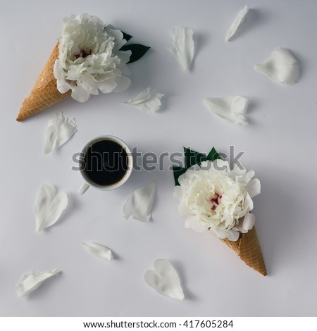 Coffee cup with flowers, icecream cones and petals. Flat lay.