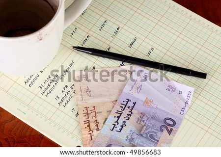 Coffee cup with general ledger sheet showing journal entries and black ballpoint pen with Moroccan one hundred dirham bill and twenty dirham bill