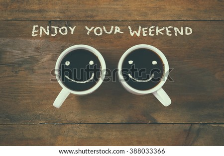 """Photo of  coffee cup with happy faces next to """"enjoy your weekend"""" phrase background. vintage filtered. happy weekend concept"""