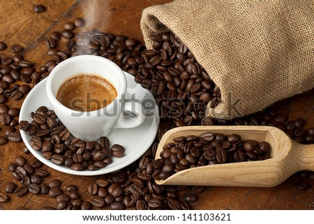 coffee cup with jute bag and spoon full of coffee beans