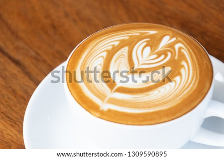 Coffee cup with latte art foam on wood table in coffee shop with copy space.Coffee is one of the most popular beverages.Improve Energy Levels and Burn Fat #1309590895