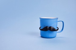 Coffee cup with mustache and bow tie on blue background. Happy Father's Day concept