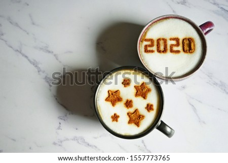 Coffee cup with number 2020 on frothy surface and another cup with star symbols flat lay on blurred marble background. Happy new year 2020 theme, Holidays food art concept for active days. (top view) #1557773765