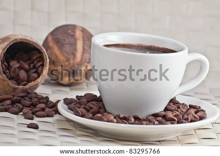 Coffee cup with roasted coffee beans, close-up