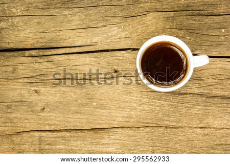 Coffee cup with roasted coffee beans on wooden table. View from top