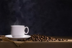 Coffee cup with saucer and scattered coffee beans on dark background. Space for text