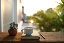 Coffee cup with small plant pot and notebook on wooden table under sunlight