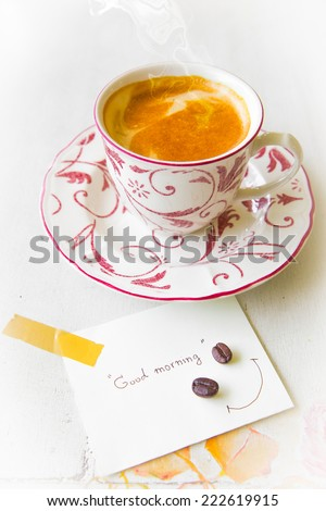 Coffee cup with smoke and good morning note on paper