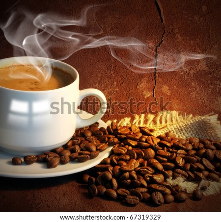 Coffee cup with smoke and grain against old wall.