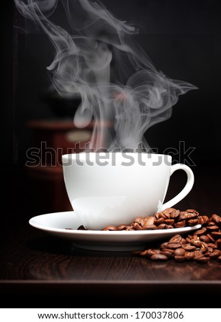 Coffee cup with smoke, grinder and grain against black wall.