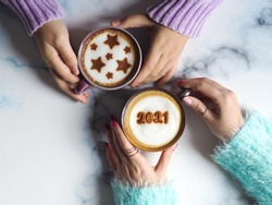 Coffee cup with the number 2021 on frothy surface in female hands holding over blurred marble table background and another one with star symbols on frothy surface. Happy new year 2021 food art theme.