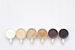 Coffee cups arranged in a creative way creating a gradient colour palette effect on white background
