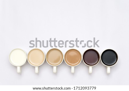 Coffee cups arranged in a creative way creating a gradient colour palette effect on white background Foto d'archivio ©