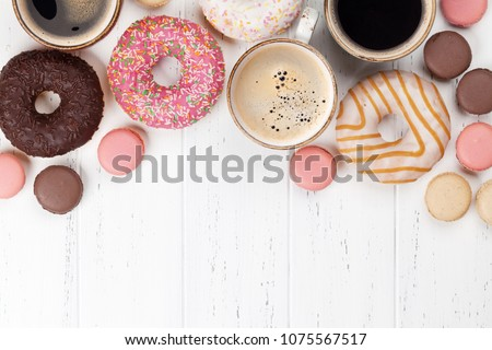 Coffee cups, donuts and macaroons on white wooden table. Top view with space for your text