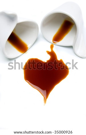 Coffee cups with heart shaped spill isolated on white background