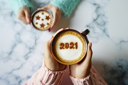 Coffee cups with number 2021 and star symbols on frothy surface in female hands holding over blurred marble table background. Holidays food art theme for happy new year 2021 celebrations. (top view)
