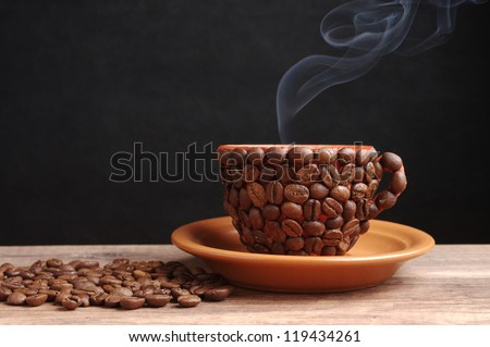 Coffee delight.  Coffee cup made from coffee beans with smoke. Black background.