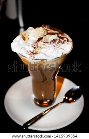 Coffee dessert with whipped cream and garnished with almond flakes. In the glass, beautiful flow. Mocha variety. #1415939354