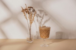 Coffee drink in a stemmed glass with a bouquet of dried flowers on a beige and white neutral background with shadows from the summer sun. Background with copy space