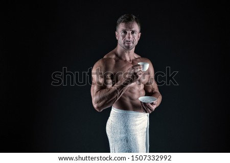 Coffee enhances athletic performance. Athletic man with fit torso drink coffee afther bath. Sexy bodybuilder hold coffee cup on black background. Black coffee gives you more energy, vintage filter.