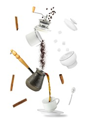 Coffee falling into cup. Flying coffee grounder and turkish brewing pot. Hot drink isolated on white background