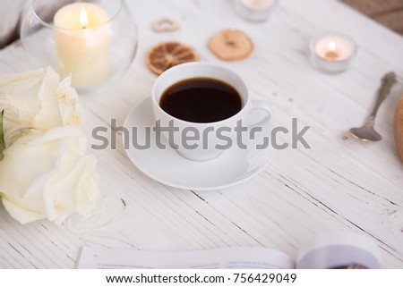 Coffee for breakfast or lunch with decorations, candles and flowers. white roses on the table and cup of coffee #756429049