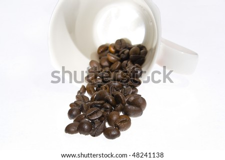 Coffee grains and coffee cup over white background
