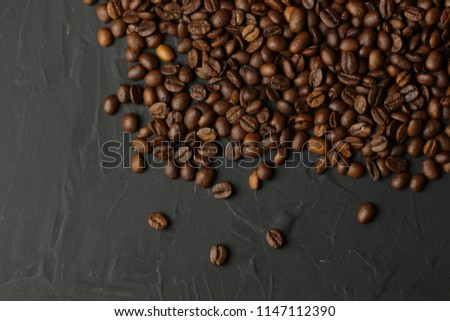 Coffee grains on a dark background. A delicious fragrant coffee of the best varieties. Coffee texture. Coffee beans background.