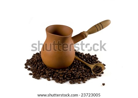 Coffee grains scattered round a coffee pot and a wooden spoon on a white background