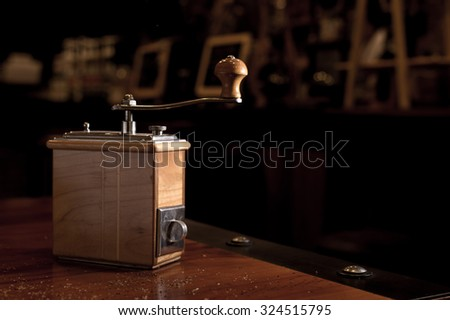 Coffee grinder. coffee maker by manual hand grinder on wood table in coffee shop.