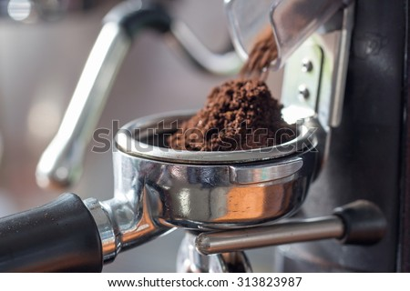 coffee grinder grinding freshly roasted coffee beans into a coffee powder