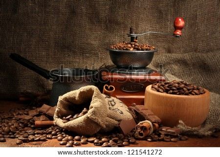 Coffee grinder, turk and cup of coffee on burlap background