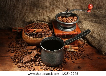 Coffee grinder, turk and cup of coffee on burlap background - stock photo