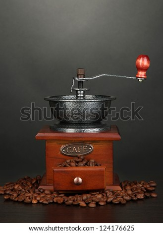 Coffee grinder with coffee beans on grey background