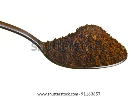 Coffee ground in a spoon isolated over white background